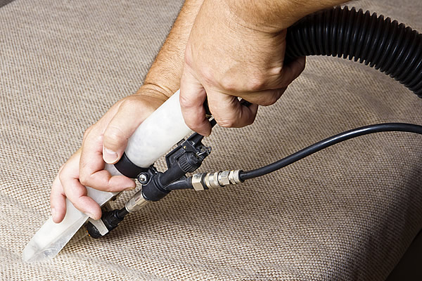 A person's hand using the upholstery attachment of a carpet cleaning machine to clean a sofa